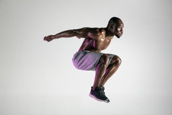 Higher than birds and faster than wind. Young african-american bodybuilder training on grey background. Muscular male model jumping in sportwear. Concept of sport, bodybuilding, healthy lifestyle.