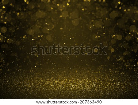 Highlighted bokeh gold sparkle glitter background. Defocused glitter stars background