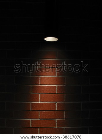 Highly contrasted spotlight on an outdoor red brick wall
