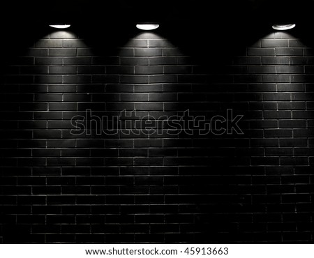 Highly contrasted spotlights on an outdoor black brick wall #45913663