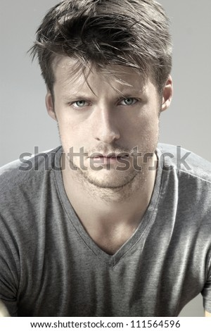 Highly detail portrait of young good looking man staring at viewer against neutral background