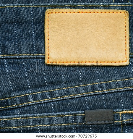 Highly detailed closeup of blank grungy leather label and small dark cotton label on striped blue denim, good for background