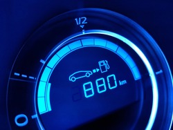 Highly efficient driving. Fuel economy gauge with indication of 880 kilometers left to refueling. Close-up of car dashboard fragment. for energy saving, carbon dioxide emission and enviromental issues