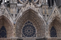 Highly sophisticated stone sculptures, lavish decorations and statuary adorning the archivolts of the porch, which also features a rose window, of the Gothic Cathedral Notre-Dame of Reims, in France