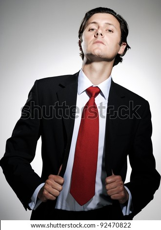Highly successful business man in suit poses pulling his suit lapels with an arrogant tilt to the chin