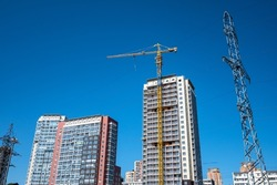 Highrise apartment buildings under construction and a jib crane in the bright blue sky background. Construction site in the new residential district