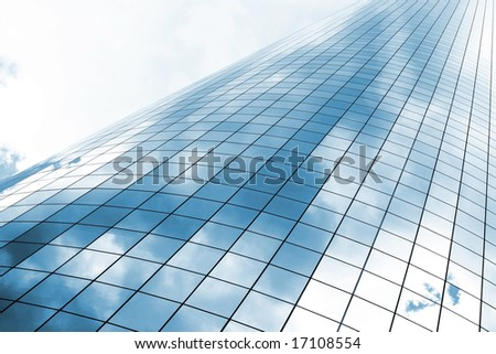 highrise glass building with sky and clouds reflection