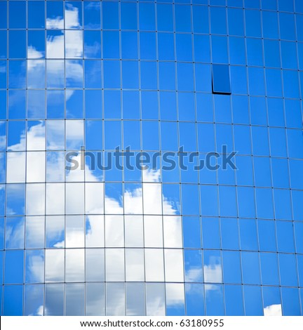 highrise glass building with sky and clouds reflection. - stock photo