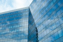 Highrise glass building with sky and clouds reflection. geometric shapes and buildings