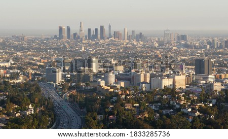Highrise skyscrapers of metropolis and busy rush hour highway, Los Angeles, California USA. Urban downtown skyline and traffic jam. Aerial view of cityscape and cars on driveway. Freeway in LA city. stock photo