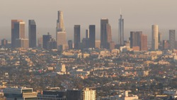 Highrise skyscrapers of metropolis in smog, Los Angeles, California USA. Air toxic pollution and misty urban downtown skyline. Cityscape in dirty fog. Low visibility in city with ecology problems.