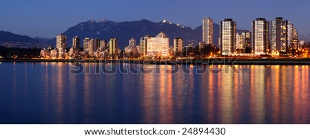 Highrises glow in gathering dusk on a winter Vancouver evening by the English Bay against a backdrop of majestic mountains.