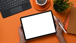 Hight angle view of woman hands holding digital tablet with white screen and stylus pen on orange background.