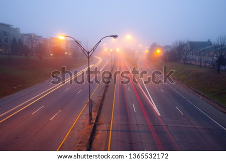 Highway at foggy night with bright trails of light from incoming and outgoing traffic. Transportation, traffic, urbanism and infrastructure concepts. #1365532172