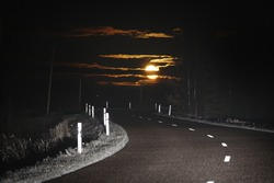 Highway at sunset. Dramatic twilight sky, midnight sun, starlight, moonlight. Dark atmospheric landscape. Panoramic view, copy space, art. Dangerous driving, loneliness, peace, freedom concepts