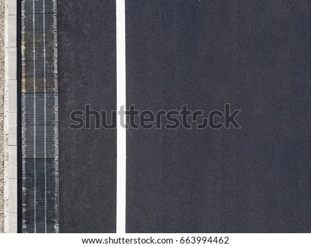 Highway background, roadside top view. Road view from above, black asphalt, white dividing strip, concrete curb, rainwater drainage system, runoff, rubble.