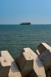 Highway breakwaters and giant freighters at sea in the distance