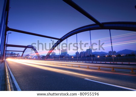 highway bridge at night with traces of light traffic