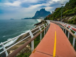 Highway by the sea. Wonderful road and bike path. Bicycle and road track and next to the blue sea in the city of Rio de Janeiro. Tim Maia bike path on Niemeyer Avenue, Rio de Janeiro, Brazil.