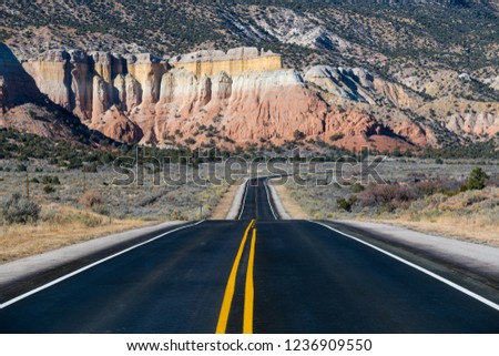 Highway curving into the distance toward colorful cliffs in near Abiquiu, New Mexico in the American Southwest #1236909550