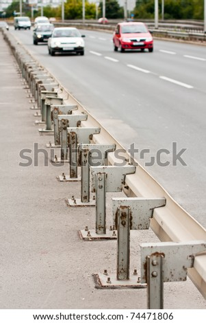 Highway guardrails with cars approaching from background
