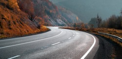 Highway in autumn mountains. Transportation background. New winding free road.
