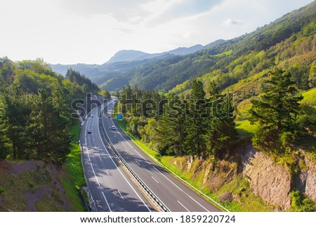 Highway in mountains with road sign and cars. Scenic curve road in autumn. Transport and traffic concept. Highway in valley, Basque country. Traffic way with beautiful landscape. Tourism in Europe.  Foto stock ©