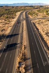 Highway in the desert with a single turnoff to the right in a horizontal view