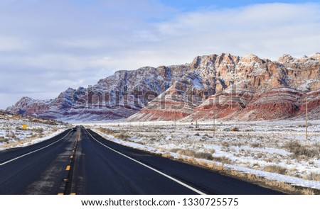 Highway 89 in the Painted Desert in northern Arizona, with light snow on the hills and blue sky. Represents freedom, travel, future.