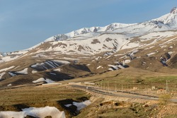 Highway leading to Erjiyes ski resort with mountain peak covered by snow