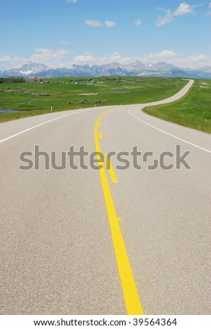 Highway on prairie to rocky mountains, waterton lakes national park, alberta, canada