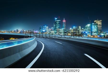 Highway overpass modern city skyline background . Night scene .