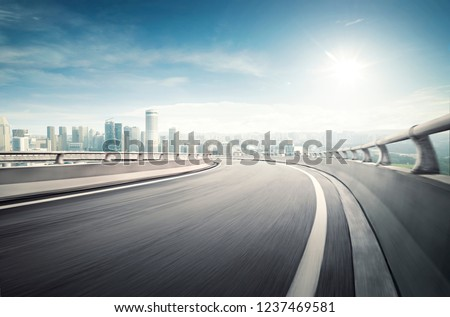 Highway overpass motion blur effect with modern city background