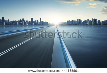 Highway overpass motion blur with city skyline background . cold mood .
