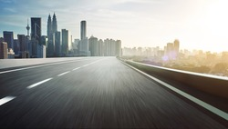 Highway overpass motion blur with city skyline background . Sunset scene .