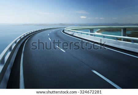 Highway overpass motion blur with coast skyline background .