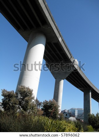 Highway overpass on large pillars towers over park below in San Francisco Mission Bay area