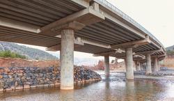 Highway overpass viaduct from below - Empty road surface floor with city overpass viaduct bridge