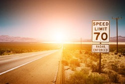 Highway road to sunset. 70 MPH speed limit sign.