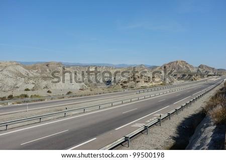 Highway running through Tabernas desert, Andalusia, Spain - stock photo
