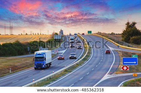 Highway traffic in sunset with cars and trucks #485362318