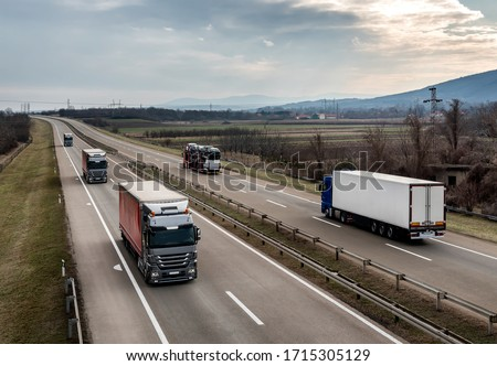 Highway transportation with a convoy of Lorry trucks passing trucks and and car transporter under a beautiful   sunset sky