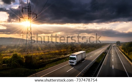 Highway transportation with white lorry at sunset