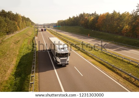 Highway. Trucks while driving, in the background a traffic control system and electronic toll collection.