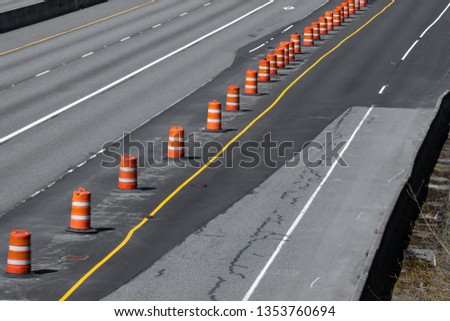 Highway under construction with a concrete roadway repaved with black asphalt, and line of orange barrel cones, in a transportation background