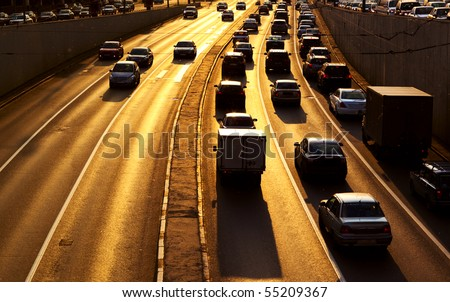 Highway with lots of cars. Red sunset light and high contrast colors.