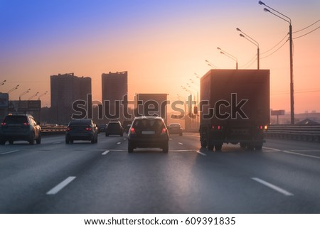 Highway with lots of cars. Truck and cars on the road on the sunset (sunrise)