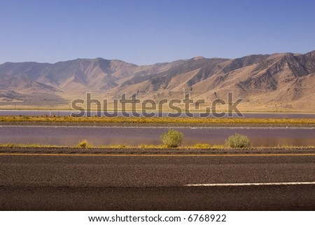 Highway with Mountains on the Background and a Stream between the lanes