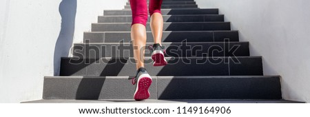 Hiit workout cardio running up the stairs training. Staircase climbing run woman going run up steps panorama banner. Runner athlete doing cardio sport workout. Activewear leggings and shoes.