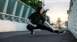 Hijab girl exercising on walkway bridge in early morning. Muslim woman wearing sports clothes doing stretching workout outdoors.